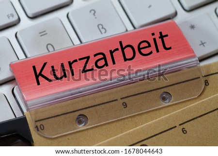 The German word for short-time work can be seen on the red label of a brown hanging folder. The hanging folder is on a computer keyboard.