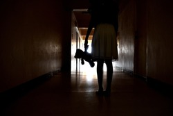 The Ghost of a little girl. Silhouette girls with a toy. A lost childhood. Bringing a child in the hallway. Creepy dark corridor. The light at the end of the tunnel. A deadly backdrop for a Thriller.
