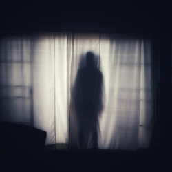 The ghost shadow standing behind the door curtain and looked into the room, blurred image.