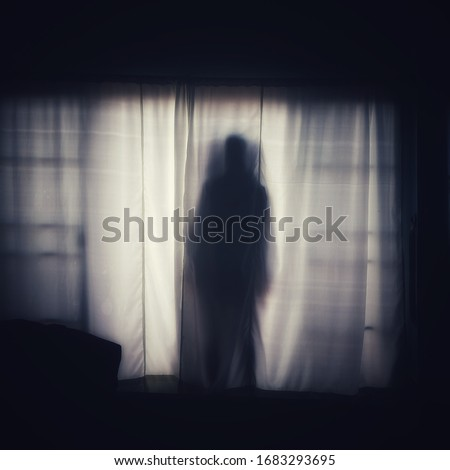 The ghost shadow standing behind the door curtain and looked into the room, blurred image. Foto stock ©