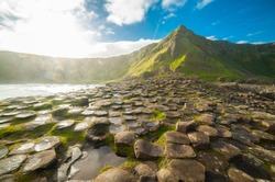 The Giant's Causeway at dawn on a sunny day with the famous basalt columns, the result of an ancient volcanic eruption. County Antrim on the north coast of Northern Ireland, UK