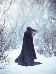 The girl a demon walks alone. She is wearing a long, black traveling cloak. Mysterious woman traveler in a black mantle in the winter forest. Violet long hair fluttering in the wind.