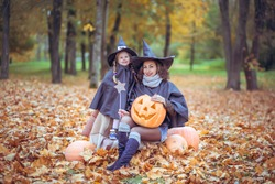 the girl and her mother in Halloween costumes with pumpkin