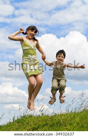 The girl and the boy jump on a green meadow