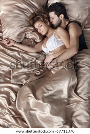 The girl and the guy sleep in a bed