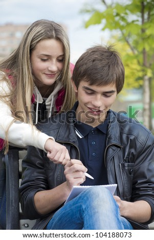 The girl and the young man write in a notebook