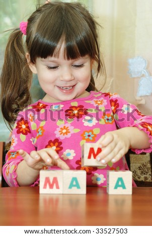 The girl and toy cubes. The child collecting a word mama from cubes.