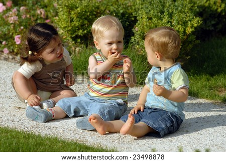 The girl and two boys walk in a park.