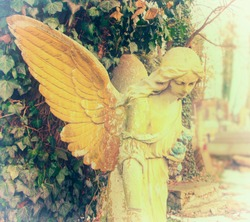 The girl angel on a light. Old stone statue (religion, Christianity, faith concept)