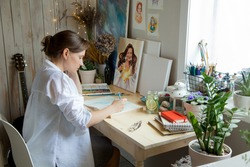 The girl artist sits at her workplace and paints portraits in watercolors. Finished works are hanging on the wall. She has a gray cat in her arms.