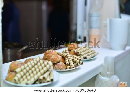 The girl at the table pours the tea into a cup. On the table lie cakes, eclairs. Traditional French dessert. Breakfast in the village. A woman is eating sweets. Against a dark background. #788958643
