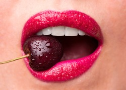 The girl bites a ripe cherry. Cherry in mouth close up. Red lipstick on lips and a cherry with water droplets. The girl is eating cherry.