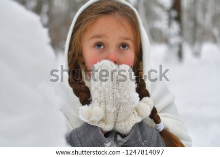 the girl  breathing warms frozen hands in mitten. portrait. Focus on mittens. Red nose and cheeks #1247814097