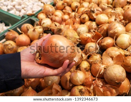 The girl buys onions on the counter in the store .