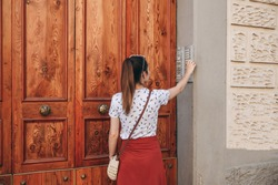 The girl calls the intercom for access inside the house.
