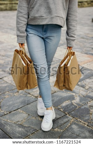 The girl carries paper bags. #1167221524