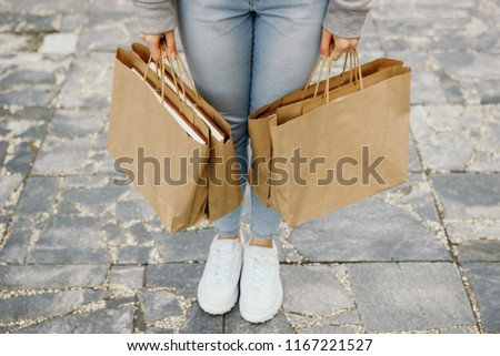 The girl carries paper bags. #1167221527