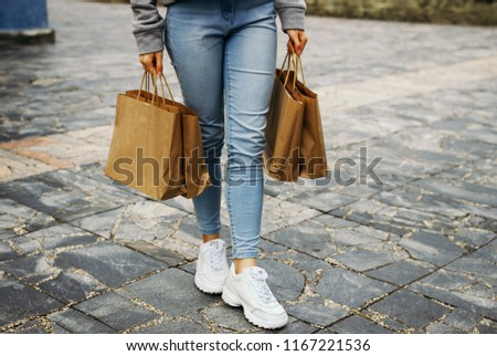 The girl carries paper bags. #1167221536