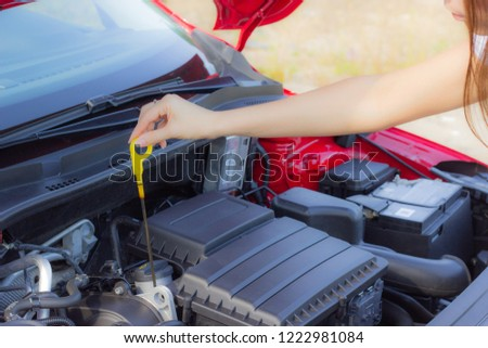 The girl checks the oil level in the car, close-up #1222981084