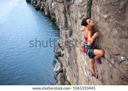 The girl climbs a climbing route over the water. extreme travel. Sport in nature. #1065310445