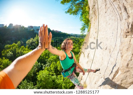 The girl climbs the rock. A woman is engaged in fitness in nature. The climber gives five companions after overcoming the climbing route. The joy of achieving the goal. Teamwork. Gesture with hand. #1288525177