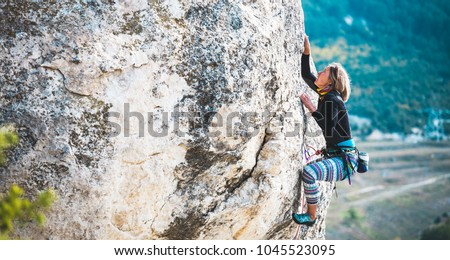 The girl climbs the rock. The climber trains on a natural relief. Extreme sport. Active recreation in nature. A woman overcomes a difficult climbing route.