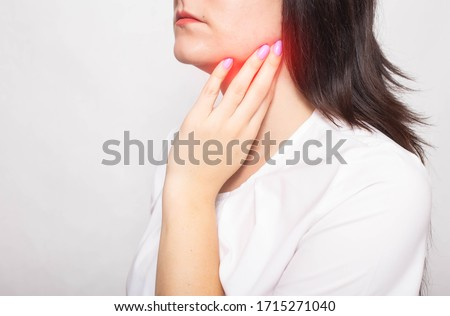 The girl clings to the inflamed salivary gland in which pain. Concept of salivary gland disease, mumps, cancer, copy space Stock photo ©