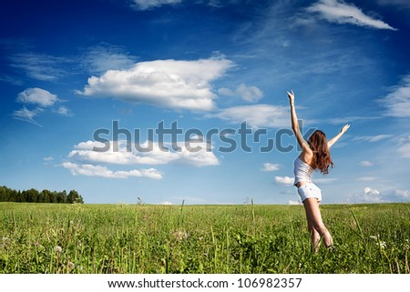 the girl costs in the field, hands are lifted in the sky