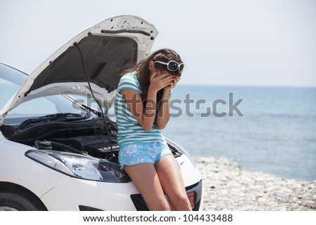 the girl cries over the broken car. Nice girl with the broken auto