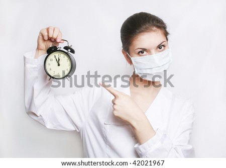 The girl-doctor shows a finger on an alarm clock.