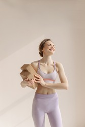 The girl does yoga. Pilates block yoga cork brick. A young woman in a sports suit on a beige one-ton background smiles.