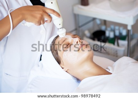 The girl doing cosmetic procedures in spa clinic - stock photo