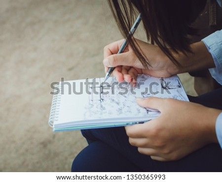 The girl draws in a notebook on the street. Close-up.