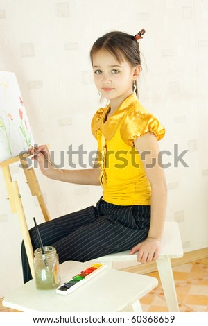 The girl draws sitting at an easel