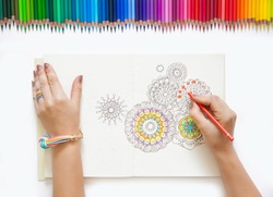 The girl draws with colored pencils. White background.