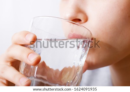 The girl drinks water from a glass. The concept of a healthy lifestyle, drinking, water quality, drinking regime.
