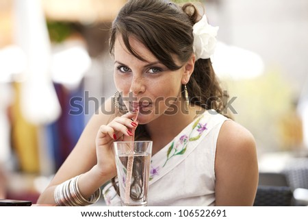 the girl drinks water from a glass through a straw. the nice European satisfies thirst in summer cafe