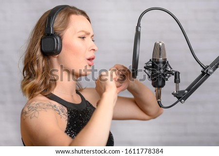 The girl emotionally reads text into a microphone, dubbing audio books, podcasts, radio, blogging and reading news