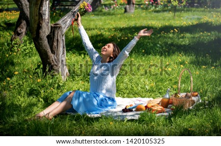 the girl enjoys nature and rest. picnic in the beautiful summer Park. the girl sits on a blanket on which a basket of food and a bottle of juice