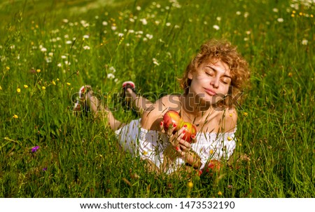 the girl enjoys nature and rest with a red apple. picnic in the beautiful summer Park.
