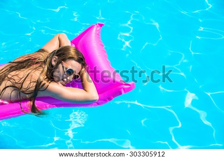 The girl floats on an inflatable mattress in the pool