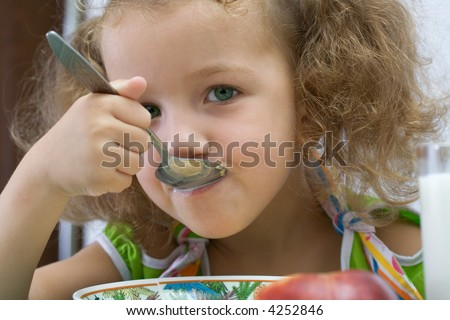 The girl has breakfast corn flakes with milk - stock photo