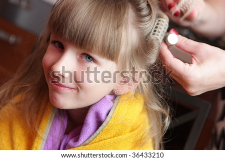 The girl has one's hair waved at home