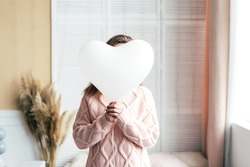 The girl hides her face behind a white balloon heart. Monochrome colors, valentine's day, faceless concept.