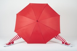 The girl hiding behind a large red umbrella
