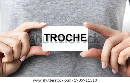 The girl holds a card with both hands with TROCHE tacts. Zdjęcia stock ©