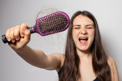 The girl holds a comb for hair with fallen hair. Hair loss, hair care.