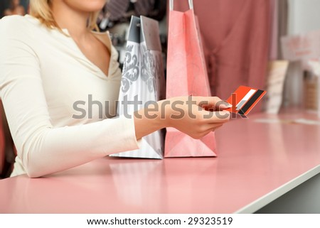 The girl holds a credit card over a counter in shop