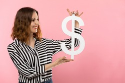 The girl holds a large dollar symbol in her hands. The shape of the US currency. Symbol of finance and cash flow in the economy and the stock market on a uniform background.