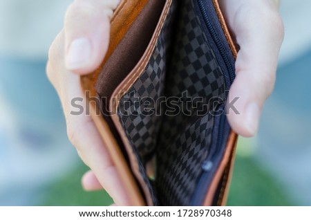 The girl holds an empty purse in her hands. Bankruptcy and crisis concept. A lack of money. Stock photo ©